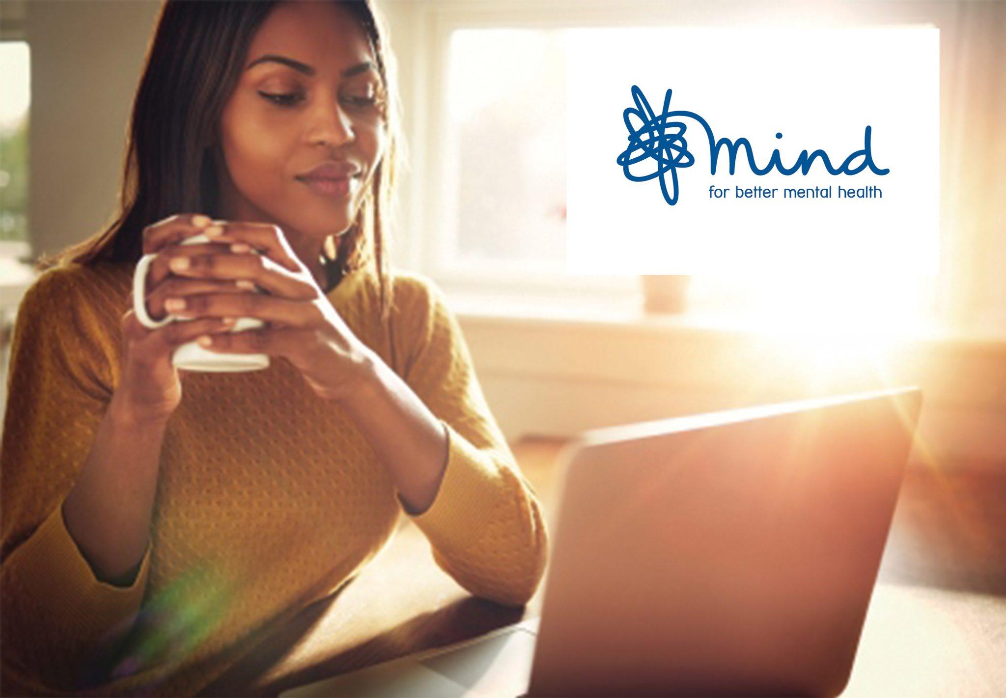 Mind logo on image of woman smiling at laptop