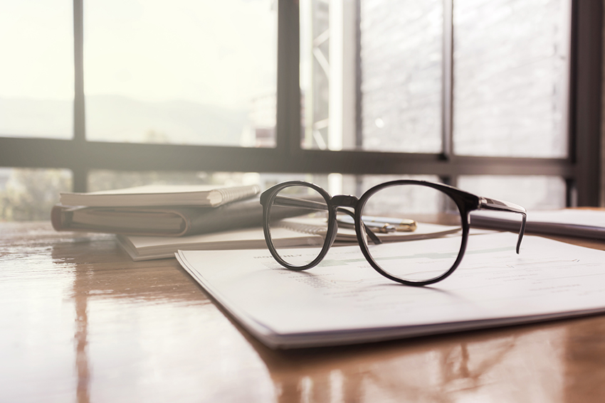 Financial advisers - glasses on paper for meeting